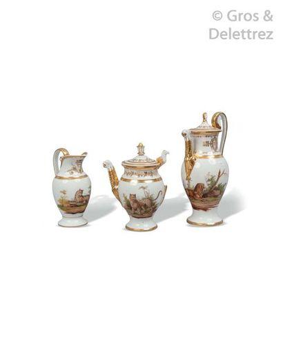 Paris. Théière, cafetière et pot à lait en porcelaine blanche et or à décor de fauves...