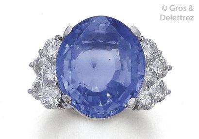 Bague en platine, ornée d'un important saphir ovale épaulé de dix diamants taillés...