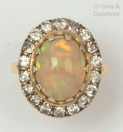 Ring in 14K yellow gold, set with an oval opal in a ring of brilliant-cut diamonds....