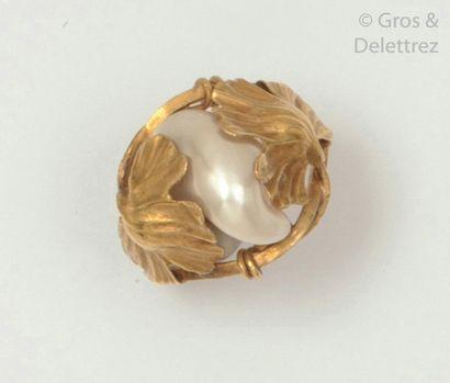 Bague en or jaune, ornée d'une perle baroque épaulée de fleurs de pavot. Travail...