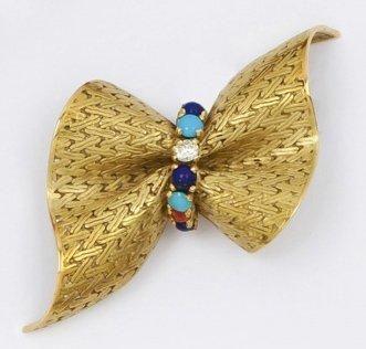 HERMES Broche «Noeud» en or jaune ornée de cabochons de turquoise, lapis lazuli et...