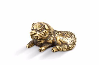 Petit lion allongé en bronze doré. Chine,...