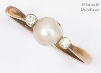 Bague en or gris ornée d'une perle épaulée...