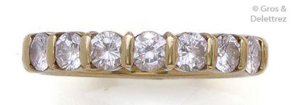 Demi-alliance en or jaune ornée de sept diamants...