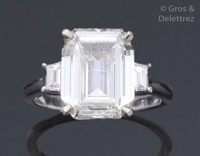 Bague en or blanc ornée d'un diamant rectangulaire à pans coupés épaulé de deux...