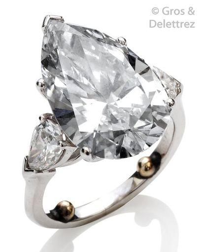 Bague en platine, ornée d'un important diamant taillé en poire épaulé de deux diamants...