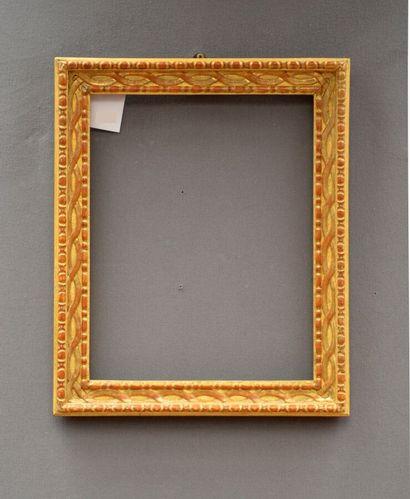 CADRE en bois sculpté et doré à décor de frise de chapelets, rubans entrelacés et...