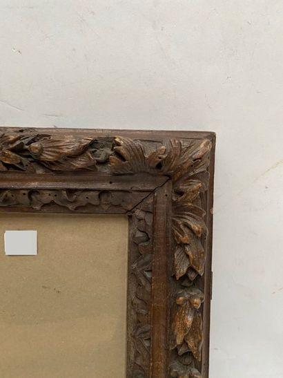 CADRE en bois fruitier, ciré et sculpté à décor de frise de feuilles d'eau et tors...