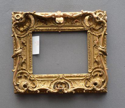 CADRE en bois sculpté et doré à riche décor...
