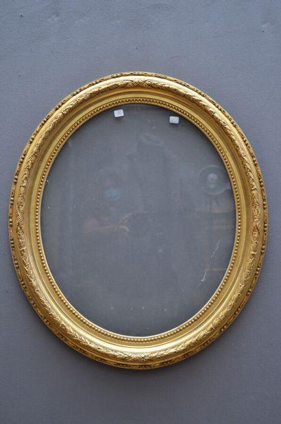 CADRE ovale en bois et stuc doré à décor de frise de perles, rais-de-coeur et frise...