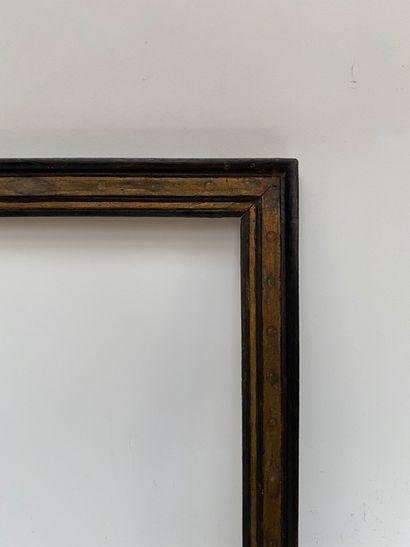 CADRE en bois mouluré noirci à fond jaune de Sienne et décor de roses dans les angles...