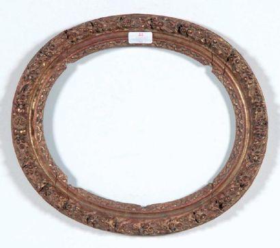 CADRE ovale en chêne sculpté et doré à décor...