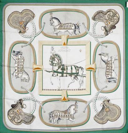 HERMES Paris CARRÉ en soie imprimée titré «Grand apparat» sur fonds gris et ivoi...