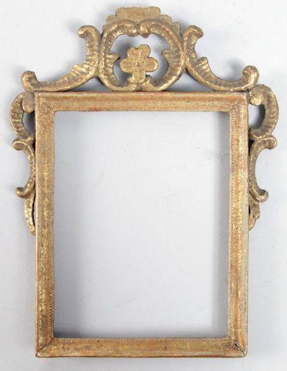 CADRE en bois doré sculpté à fronton ajouré à motif de fleurette et agrafes d'époque...