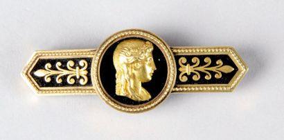 BROCHE en or jaune et onyx de style Empire à motif de profil antique et de fleurons....