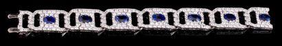 Bracelet Art Déco en or gris formé de maillons enlacés pavés de diamants et centrés...