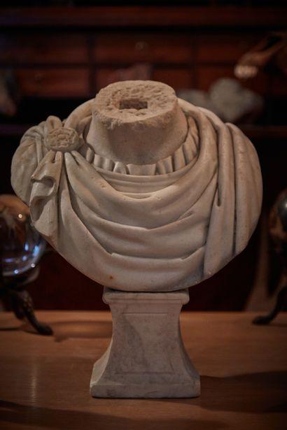 Buste acéphale en marbre sculpté d'un drapé à l'antique dit chlamyde, retenue par...