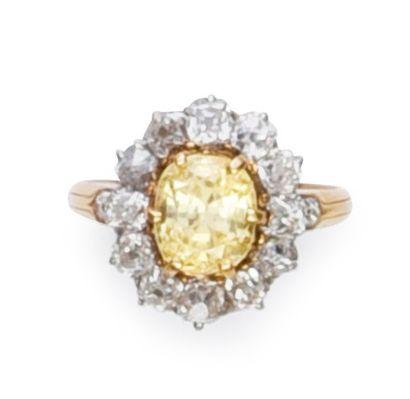 Bague marguerite en or 750°°, serti d'un saphir jaune dans un entourage de diamants...
