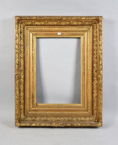 Beau cadre en bois et stuc doré à riche décor...