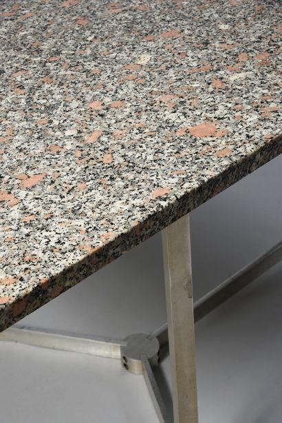 Table de salle à manger. Le plateau en granit rose repose sur quatre pieds en inox...