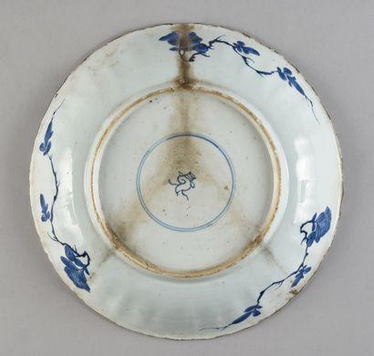 CHINE Grand plat en porcelaine à décor blanc et bleu d'un panier fleuri entouré d'une...