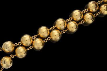 Un collier de boules en or, reliées par de...