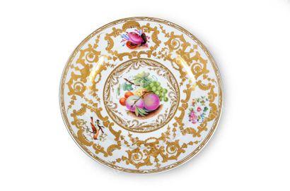 Assiette plate en porcelaine. A décor polychrome de fruits dans un médaillon central,...