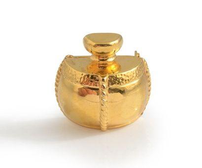Yves Saint LAURENT Broche en métal doré représentant le flacon d'un parfum.