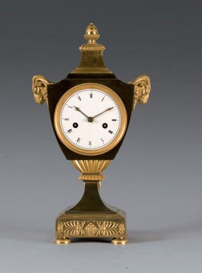 Pendule en bronze patiné et doré, en forme...