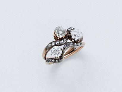 Bague en or 750 millièmes, la monture en vague ponctuée de roses diamantées, décorée...