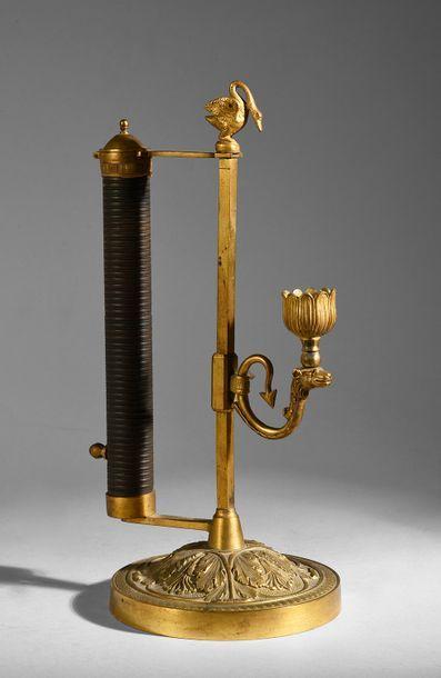 Flambeau en bronze ciselé, doré et patiné,...