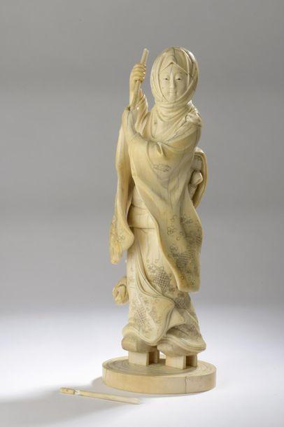 Okimono en ivoire sculpté et rehaussé à l'encre,...