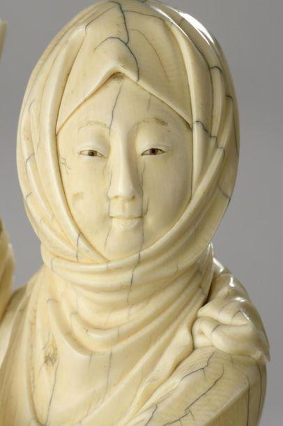 Okimono en ivoire sculpté et rehaussé à l'encre, femme debout sur de hautes geta,...