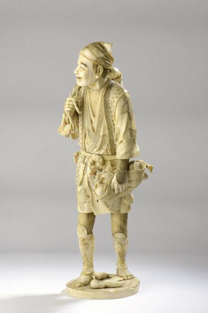 Okimono en ivoire de morse sculpté et rehaussé à l'encre, figurant un paysan portant...