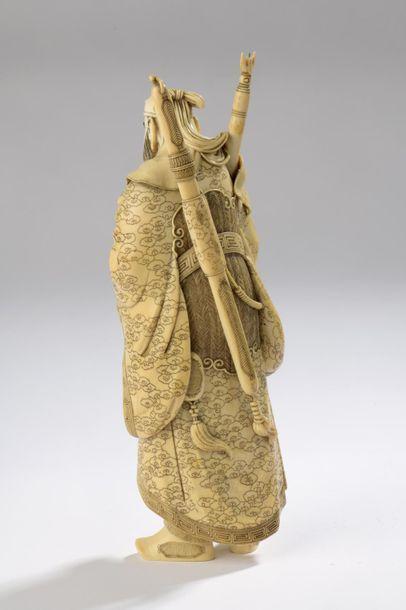 Sujet en ivoire, Kwanyu debout, le regard sévère, son épée dans le dos, une lance...