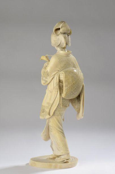 Okimono en ivoire, jeune femme debout, un panier de victuailles à la main, le kimono...