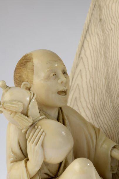 Groupe en ivoire, un homme debout tenant une biwa et un éventail, un autre assis...