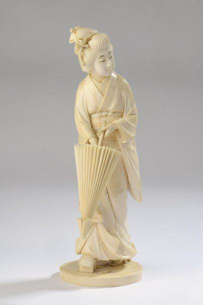 Sujet en ivoire, bijin (belle femme) debout, de hautes geta aux pieds, un parasol...