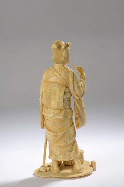Okimono en ivoire à belle patine jaune, jeune femme debout, une houe dans la main...