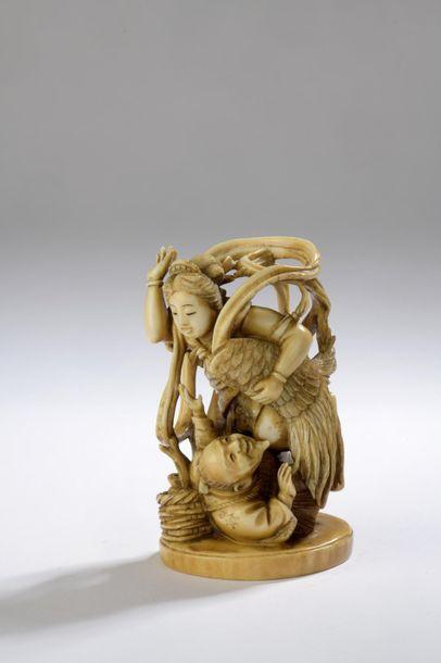 Okimono en ivoire à patine jaune, Tennin tenant ses ailes sous son bras gauche,...
