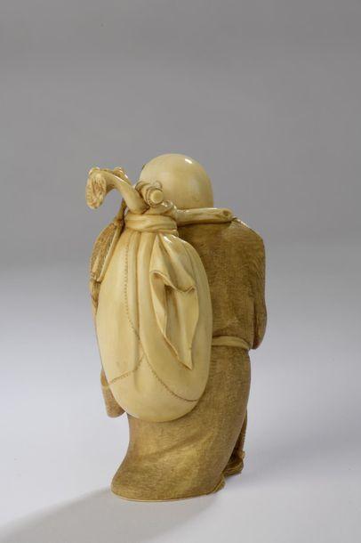 Okimono en ivoire, Hotei debout, le visage hilare, son sac des richesses dans le...