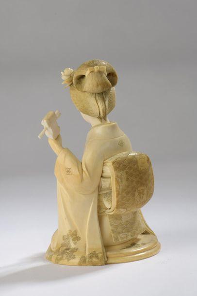 Okimono en ivoire, jeune femme jouant du shamisen, son kimono très finement ciselé...