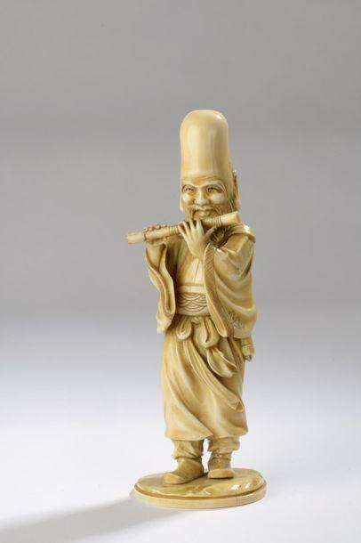 Okimono en ivoire figurant Fukurukuju debout, jouant de la flûte. Socle en ivoire....