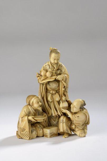 Okimono en ivoire à patine jaune, trois personnages...
