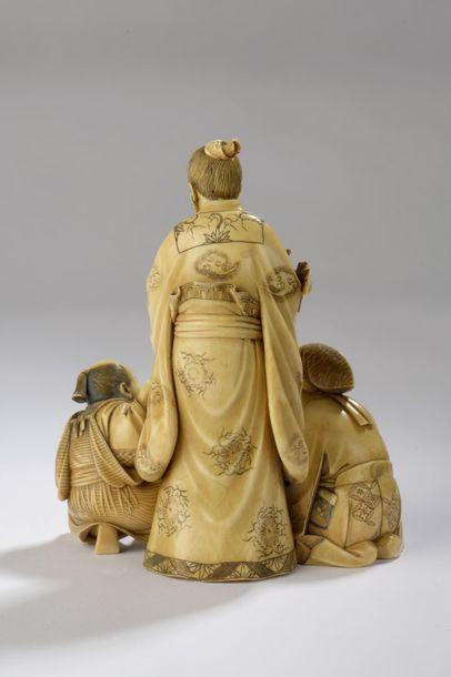 Okimono en ivoire à patine jaune, trois personnages dont un taoïste qui tient une...