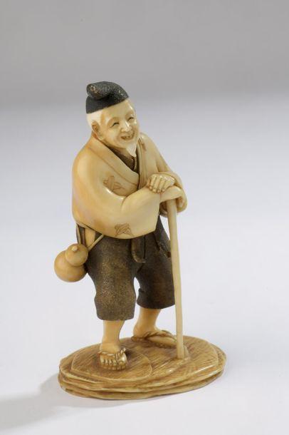 Petit okimono en ivoire de mammouth, vieillard debout se reposant sur une canne,...