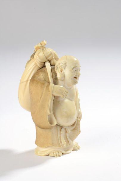 Sujet en ivoire, Hotei debout, son énorme sac et son éventail dans le dos. Signé...