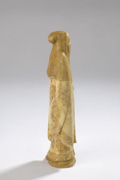 Sujet en ivoire de morse, homme debout, sa robe richement décorée de motifs floraux....