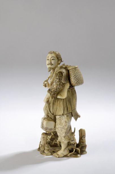 Okimono en ivoire, voyageur debout, un panier dans son dos et un coffret au bout...