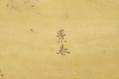 Okimono en ivoire, homme assis sur un panier, fumant la pipe, la tête tournée vers...